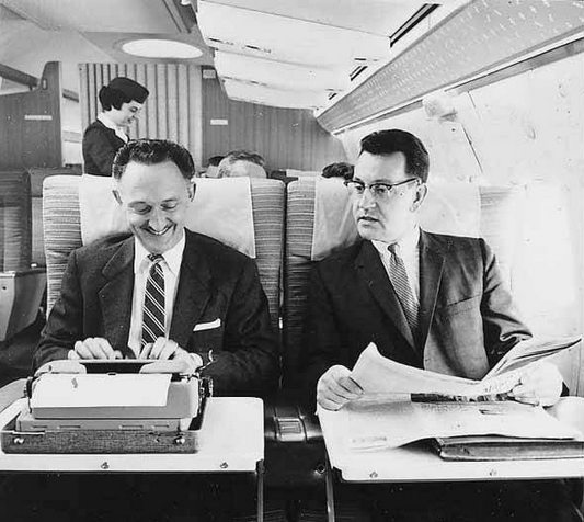 Two men on Northwest Airlines aircraft, one using typewriter, with female flight attendant in background, ca 1965.
